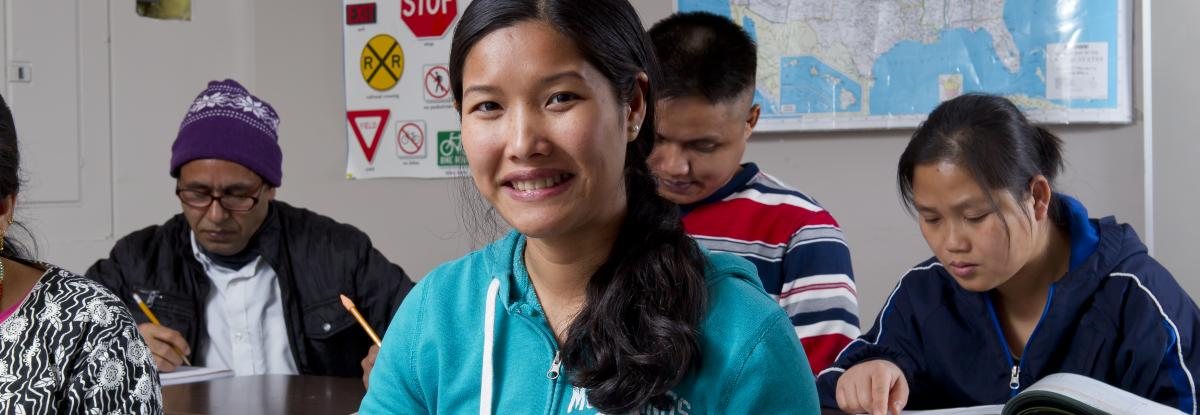 A woman smiles at the camera while students behind her are busy studying.